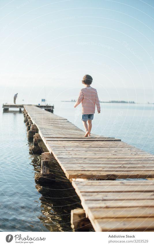 Einsames Kind am Pier bei Sonnenschein Junge Anlegestelle laufen träumen Sommer Sonnenlicht Ferien & Urlaub & Reisen Kindheit Wasser Natur Freizeit & Hobby