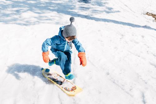 Kind springt an Bord und fährt einen verschneiten Berg hinunter Junge Holzplatte Schnee Rutsche Geschwindigkeit klein Winter Ausritt Sport abwärts Aktion