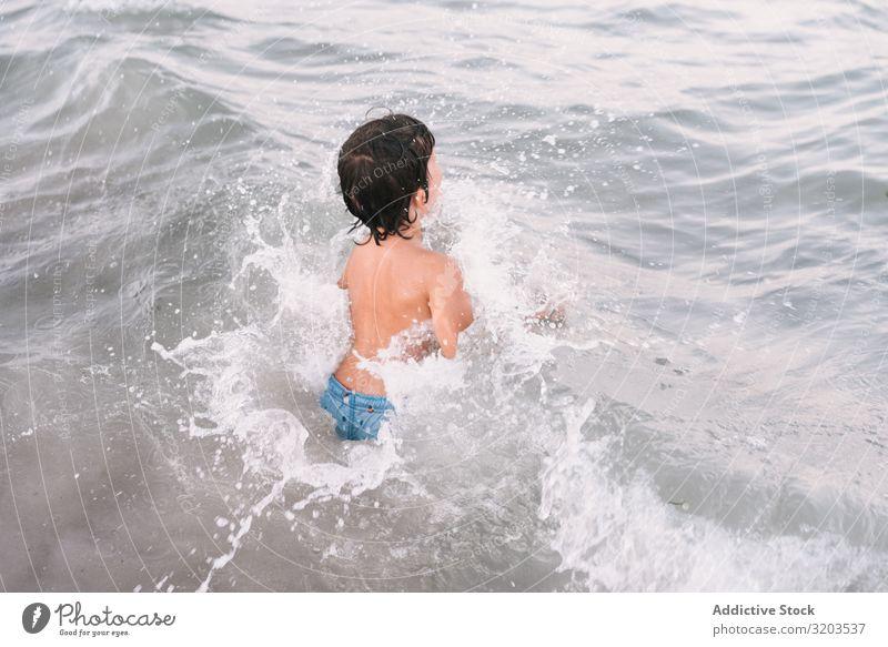 Junge, der im blauen Wasser des Kurortsmeers spazieren geht Meer Strand laufen Sommer Kindheit erkunden Freizeit & Hobby klein Ferien & Urlaub & Reisen Freude