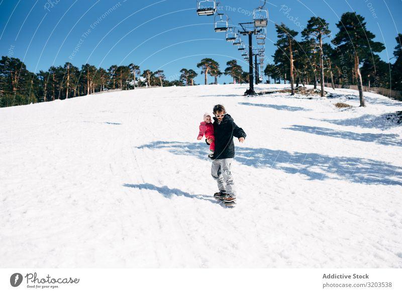 Mann mit Tochter reitet auf Schnee Holzplatte Ausritt Freiheit Kind Natur Kleinkind Winter Rutsche Aktion Berge u. Gebirge Unbekümmertheit erkunden Sport Resort