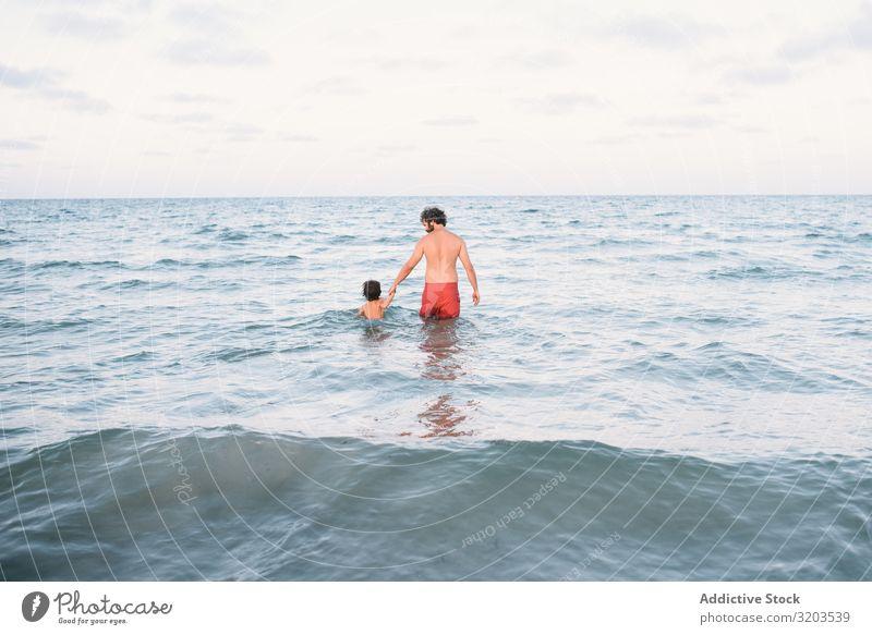Vater mit Sohn im Wasser laufend Mann Im Wasser treiben Küste Zusammensein Händchen haltend Junge Familie & Verwandtschaft Aktion Strand