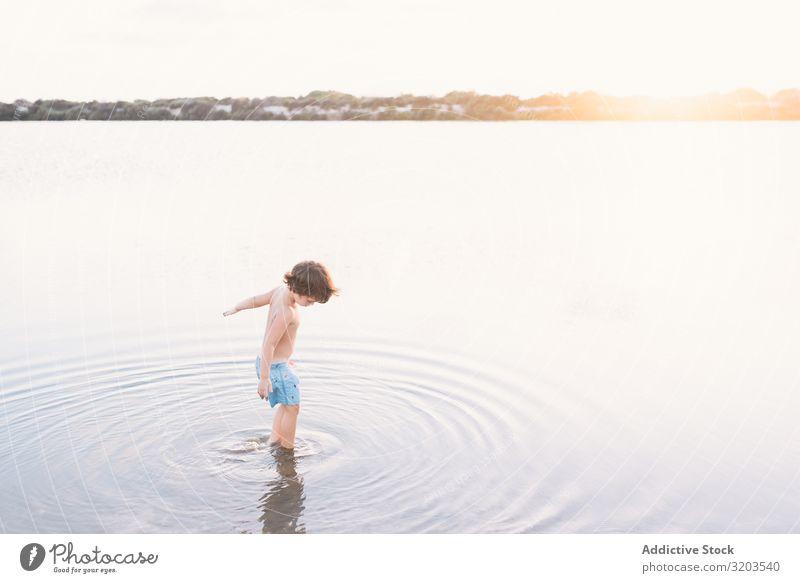 Junge geht im Wasser des Sees Strand Sommer erkunden laufen Kind Sonnenuntergang Kindheit Freizeit & Hobby Ferien & Urlaub & Reisen hell träumen Einsamkeit