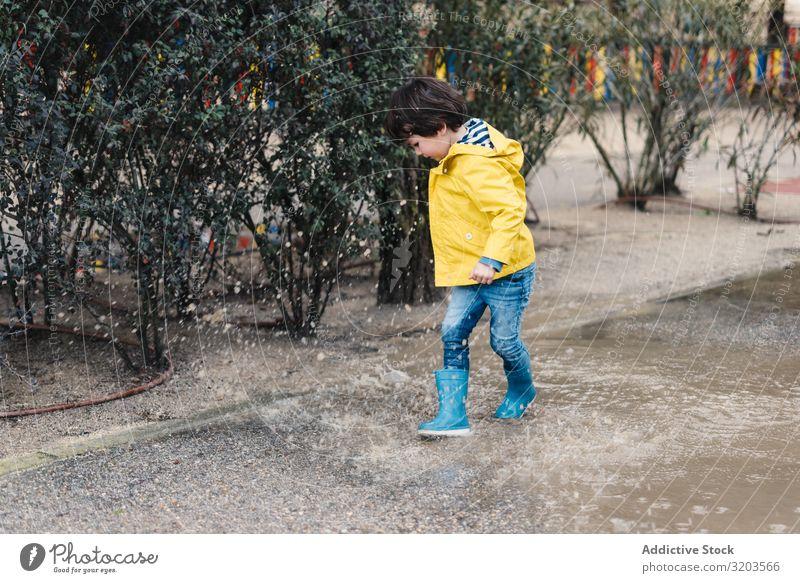 Glückliches Kind springt auf Pfütze Junge springen Freude Straße Gummistiefel nass Wasser spielerisch Kindheit Herbst Wetter Natur Spielen Regenmantel