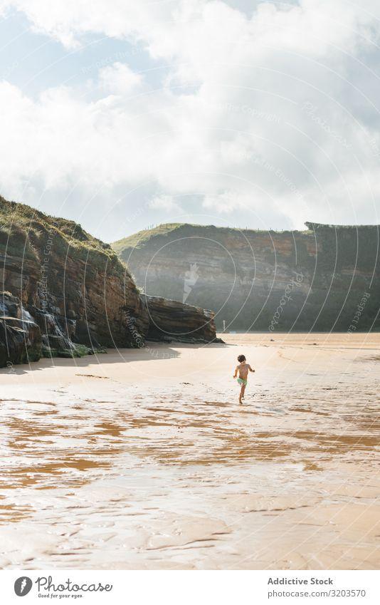 Junge, der am nassen, sonnigen Strand spazieren geht Sonnenlicht Kind Sommer Küste Wasser unschuldig Ferien & Urlaub & Reisen Freizeit & Hobby Baby Spielen