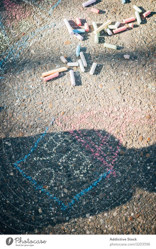 Farbige Kreide auf dem Bürgersteig an einem sonnigen Tag Kunst Gemälde Asphalt Kreativität Straße Spielplatz mehrfarbig Kindheit Spielen künstlerisch Aktion