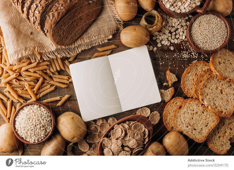 Vollkornprodukte und frisch gebackenes Roggenbrot auf dem Tisch Brot Kartoffeln Haferflocken Zerealien Mahlzeit Haferbrei Notizbuch appetitlich geschmackvoll