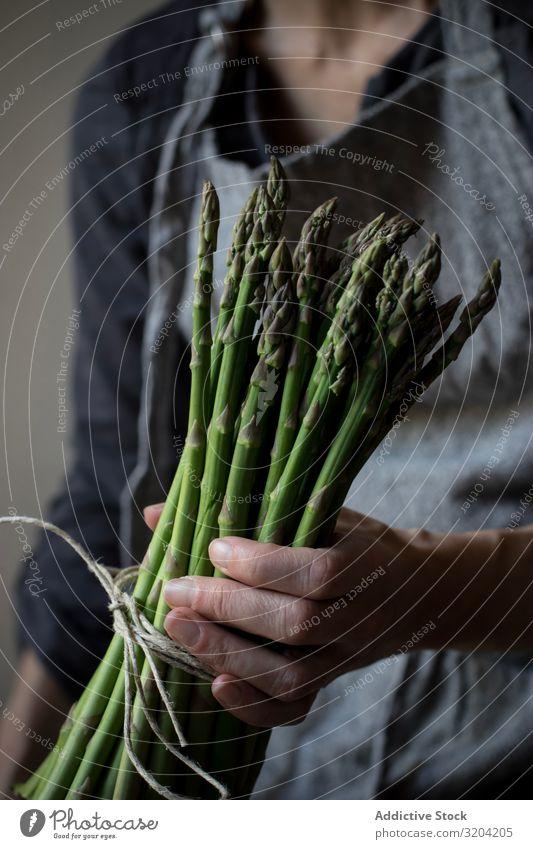 Gesichtslose Frau mit einem Bündel grünen Spargels rustikal Hand Halt organisch Diät Lebensmittel natürlich Ernährung roh Zutaten Vegetarische Ernährung