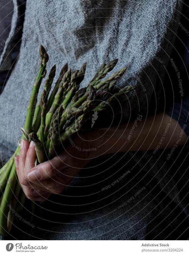 Gesichtslose Frau mit einem Bündel grünen Spargels rustikal Hand Halt organisch Diät Lebensmittel natürlich Ernährung roh Zutaten Vegetarische Ernährung zart