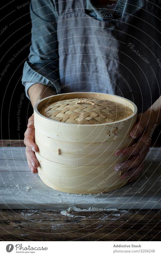 Person, die einen Bambus-Dampfer hält vereinzelt Dim Sum Küchengeräte Container Kasten Wasserdampf Utensil Korb Orientalisch Objektfotografie Deckel überdeckt