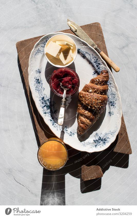 Servierte Frühstücksmahlzeit mit Sandwich und Marmelade Croissant Saft Erdbeeren Orange Butter frisch lecker Lebensmittel Dessert Ernährung Mahlzeit trinken