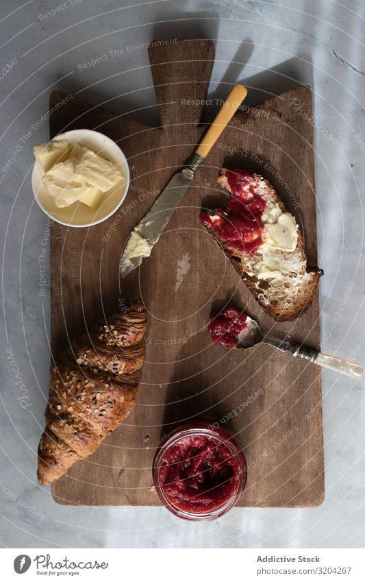 Servierte Frühstücksmahlzeit mit Sandwich und Marmelade Croissant Erdbeeren Butter frisch lecker Lebensmittel Toastbrot Dessert Ernährung Mahlzeit Frucht