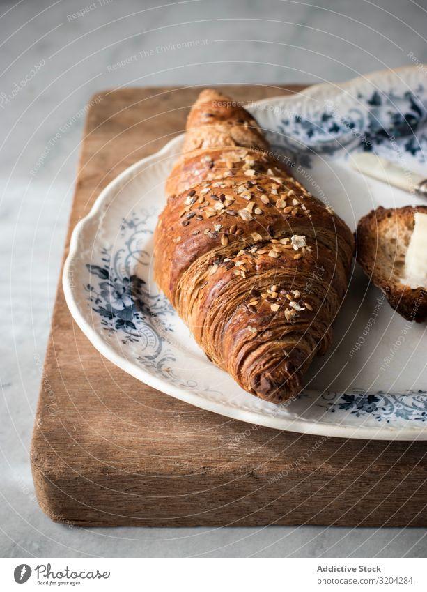 Knuspriges Croissant mit Körnern Getreide lecker Teller Frühstück Snack Lebensmittel Brötchen geschmackvoll Morgen braun Brot frisch Essen zubereiten süß backen