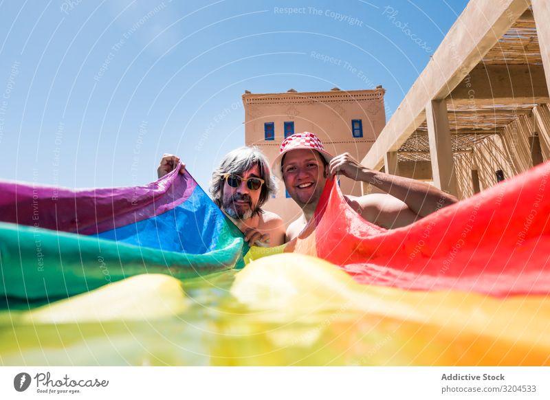 Glückliches schwules Paar im Schwimmbad Homosexualität lgbt Fahne Übergewicht Zusammensein Liebe Resort Ferien & Urlaub & Reisen Wasser Mann versteckend