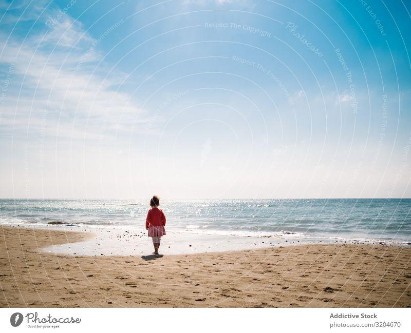 Mädchen, das am sonnigen Tag am Strand spazieren geht laufen Sonnenstrahlen Kleinkind Sand Seeküste Wasser ruhig Küste Kindheit Ferien & Urlaub & Reisen Aktion