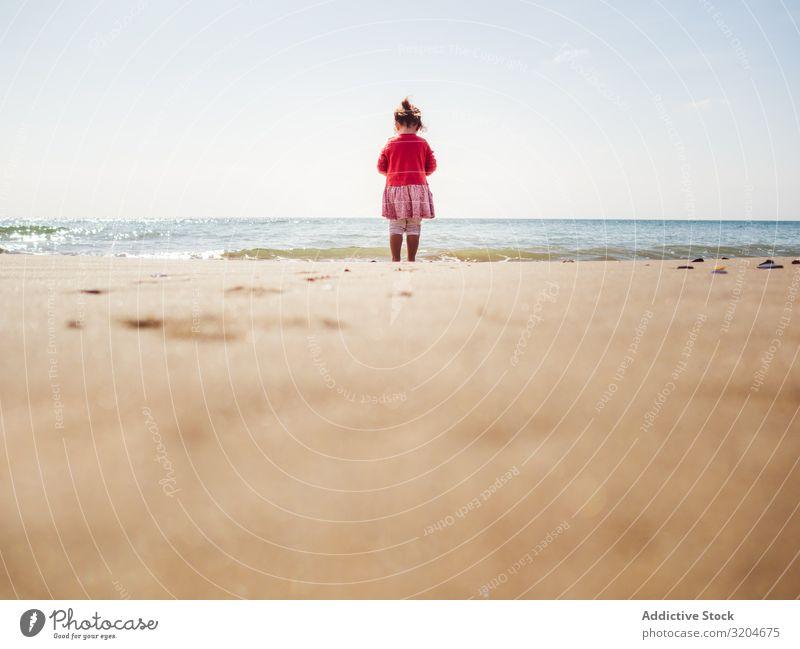Mädchen, das an einem sonnigen Tag am Strand spazieren geht laufen Sonnenstrahlen Kleinkind Sand Seeküste Wasser ruhig Küste Kindheit Ferien & Urlaub & Reisen
