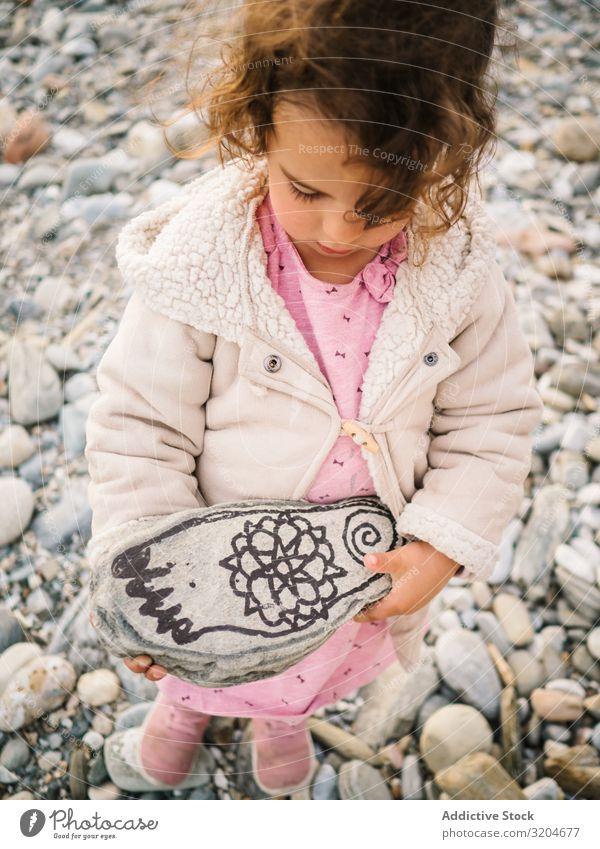 Mädchen hält bemalten Stein beim Spielen am Strand Kleinkind Interesse niedlich Kindheit Seeküste Verstand Kreativität Gelassenheit Küste