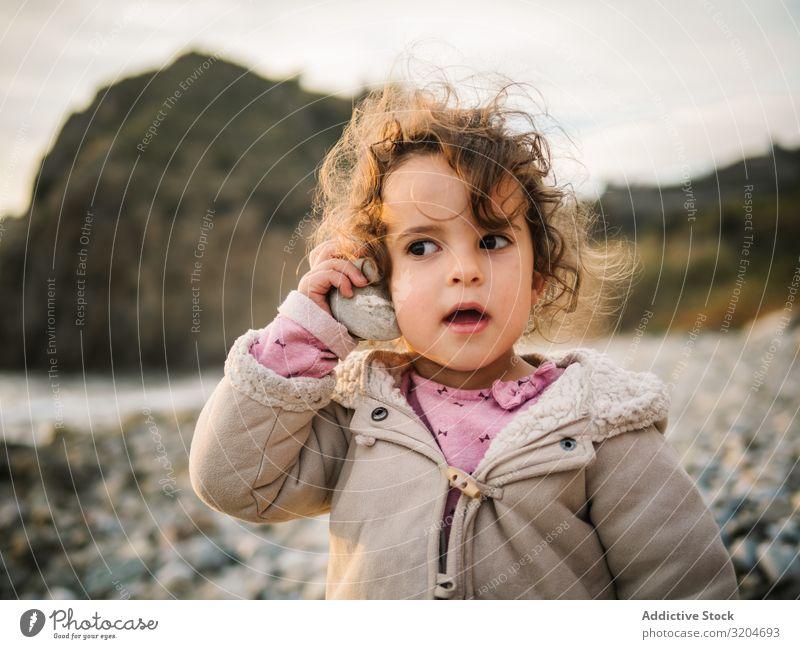 Kleinkind spielt mit Muschel am Strand Mädchen Spielen Kind Aufmerksamkeit entzückt Porträt hören aussruhen Natur Interesse Fundstück verblüfft Freizeit & Hobby