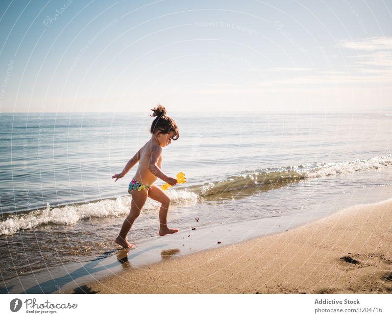 Kleinkind, das am Sandstrand spazieren geht Mädchen Strand laufen Spielen Kind Schwimmsport Meer ruhig Kindheit Sommer Ferien & Urlaub & Reisen Sonnenstrahlen