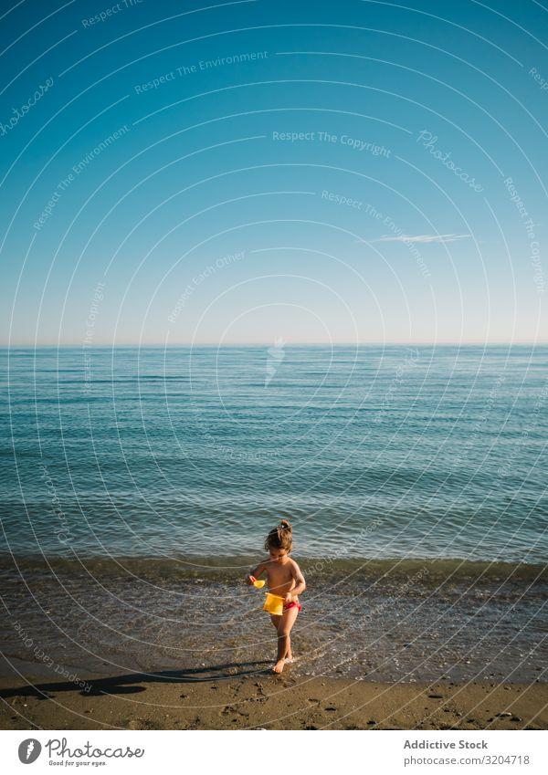 Mädchen spielt mit kleinen Steinen am Strand Spielen Kleinkind Sand Küste ruhig Meer Sonnenstrahlen Seeküste Wasser Kindheit Ferien & Urlaub & Reisen Aktion