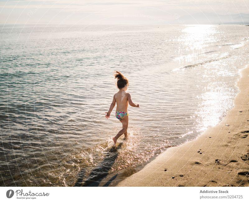 Anonymes Mädchen läuft am Meer rennen Strand Schwimmen & Baden platschen Kind Schwimmsport Sand ruhig Spielen Kindheit genießend Aktion Sommer Kleinkind
