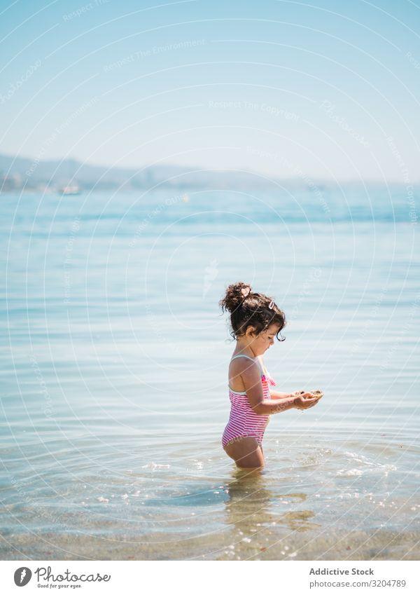 Süßes Mädchen spielt im Wasser der Küste Spielen Seeküste niedlich Kleinkind reizvoll Meer Badeanzug Wärme Strand Sonnenstrahlen Kindheit Schwimmen & Baden