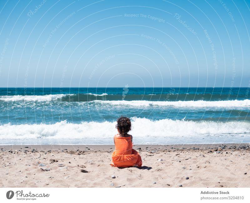 Kleines Mädchen sitzt am Strand und bewundert die Aussicht Kind bewundernd sitzen Seeküste Sand Meer Himmel klein Frau Orange Kleid Blick schön Sommer winken