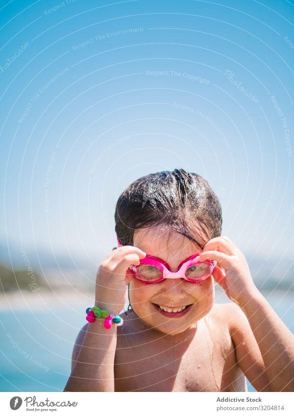 Fröhliches Mädchen mit Schutzbrille nach dem Schwimmen im Meer Schneebrille heiter niedlich Lächeln Kind abfliegend Blauer Himmel Frau Sommer Glück