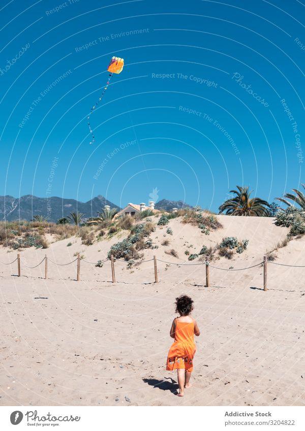 Kleinkind spielt mit Drachen am Sandstrand Mädchen Lenkdrachen Strand Spielen klein Kind Frau fliegen Blauer Himmel rennen Seeküste Ferien & Urlaub & Reisen