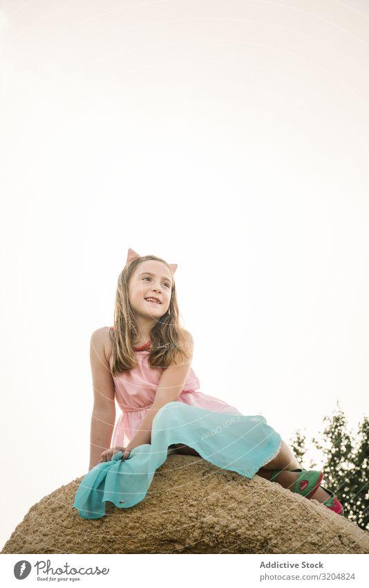 Verträumtes, süßes Mädchen auf einem Felsen sitzend träumen Natur Kind Sommer Kindheit niedlich Kleid schön Beautyfotografie Zeitgenosse erkunden unschuldig