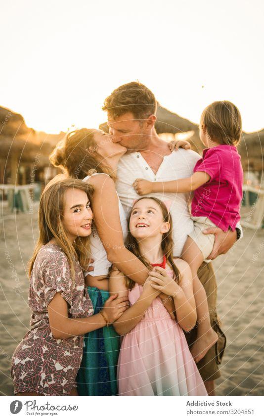 Schöne glückliche Familie mit Kindern am Strand Familie & Verwandtschaft Eltern Liebe Küssen Glück Menschengruppe Geschwisterkind Sommer
