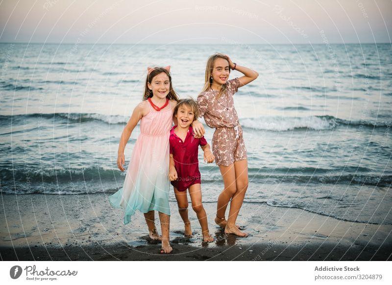 Kinder, die im flachen Wasser spielen Strand winken Familie & Verwandtschaft Sommer Menschengruppe Zusammensein Geschwisterkind Glück Aktion