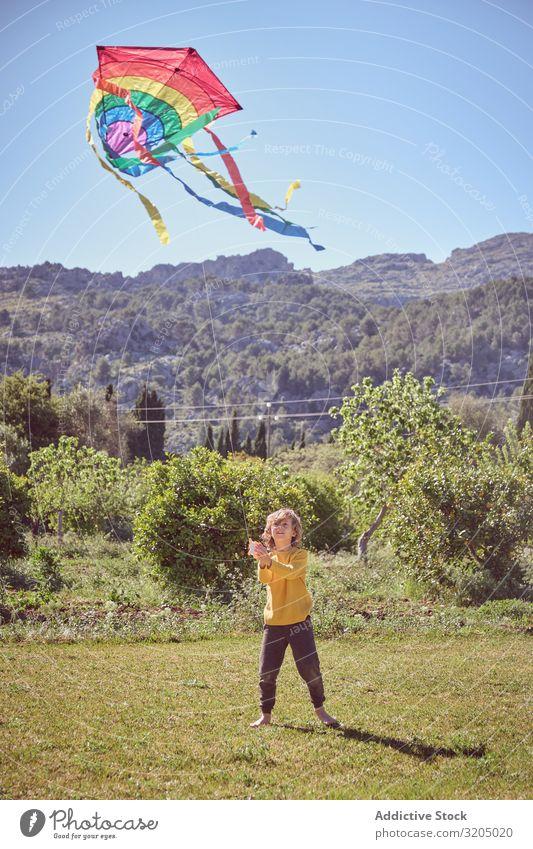Junge startet Drachen am Sommertag Lenkdrachen Himmel Freude Kindheit Spielen fliegen Landschaft klein Mensch Aktion spielerisch lässig Unbekümmertheit heiter