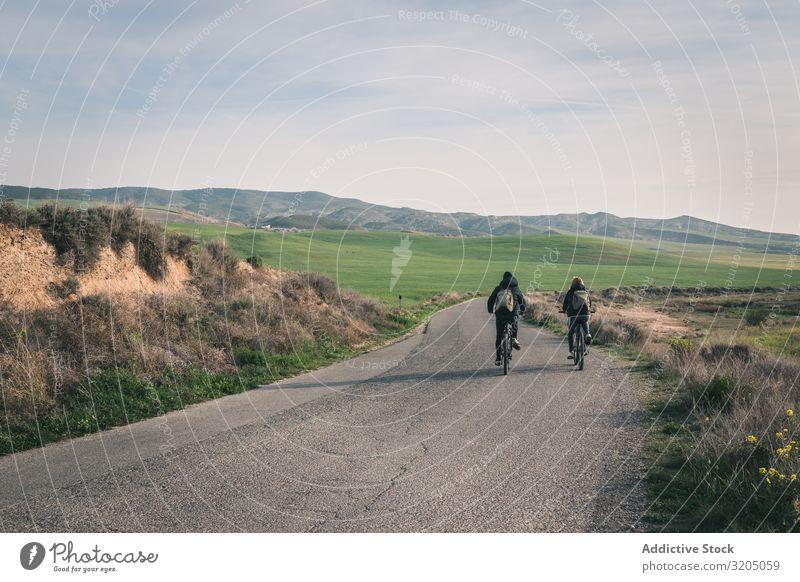 Männer mit dem Fahrrad auf der Straße in den Wüstenhügeln Mann Hügel Landschaft Sand Stein Pflanze Ausflug regenarm Natur Himmel Ferien & Urlaub & Reisen heiß