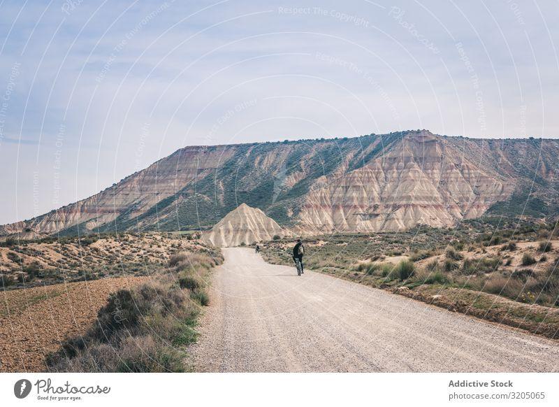 Mann fährt Fahrrad auf der Straße in den Wüstenhügeln Hügel Landschaft Sand Stein Pflanze Ausflug regenarm Natur Himmel Ferien & Urlaub & Reisen heiß