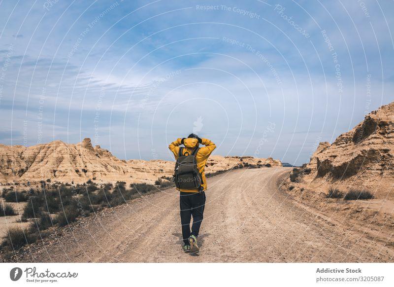 Mann auf der Straße in den Wüstenhügeln Hügel Landschaft Sand Stein Pflanze Ausflug regenarm Natur Himmel Ferien & Urlaub & Reisen heiß Ausflugsziel erkundend