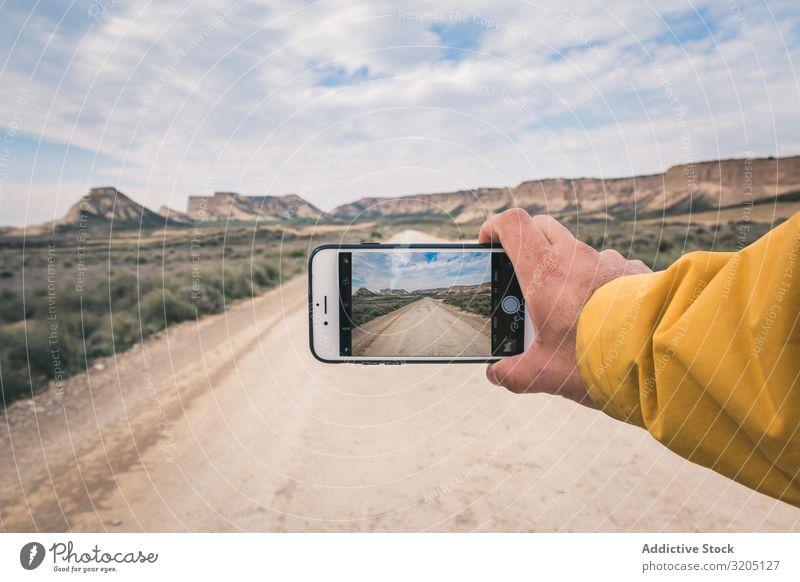 Person, die eine leere Straße und Wüstenlandschaft fotografiert Mann fotografierend Hügel Landschaft Sand Stein Pflanze Ausflug PDA regenarm Natur Himmel