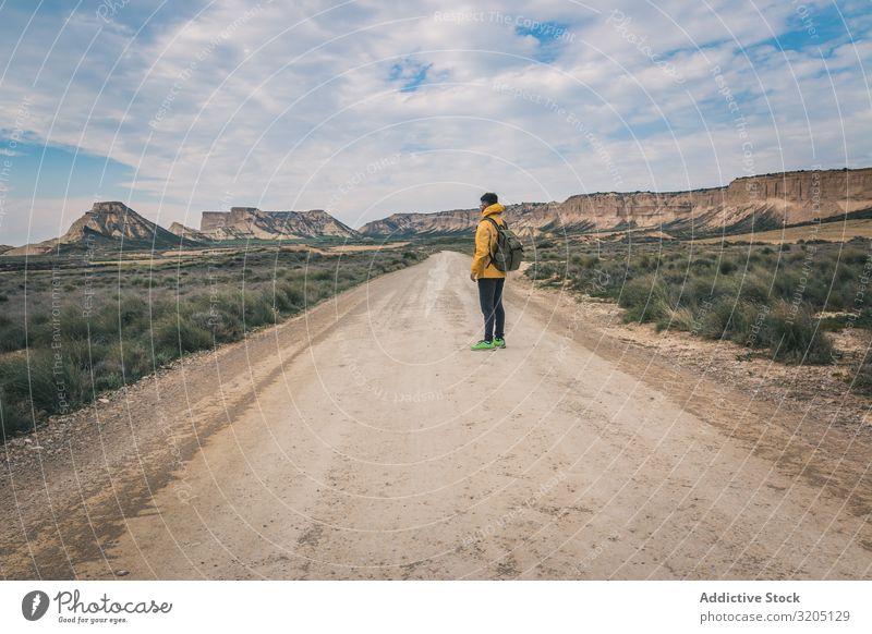 Mann steht auf der Straße in den Wüstenhügeln Hügel Landschaft Sand Stein Pflanze Ausflug regenarm Natur Himmel Ferien & Urlaub & Reisen heiß Ausflugsziel