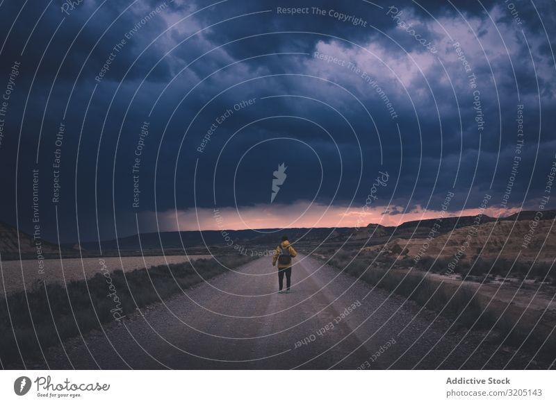 Mann steht auf der Straße und schaut in den beeindruckenden Abendhimmel Dämmerung Wüste Landschaft Sand Stein Ausflug Abenddämmerung Natur Himmel