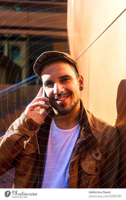 Mann benutzt Mobiltelefon in modernem Gebäude selbstbewußt Wand anlehnen Stil Sonnenstrahlen Tag Jugendliche lässig trendy Erfolg Coolness positiv Lifestyle