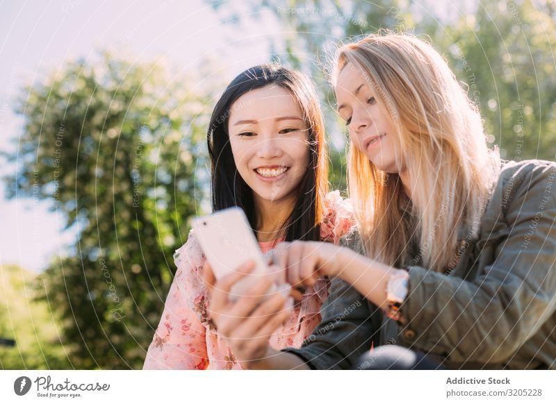 Freundinnen, die im Park ein Smartphone benutzen Freundschaft PDA benutzend zeigen Lächeln Person gemischter Abstammung Frau Jugendliche Mitbenutzung