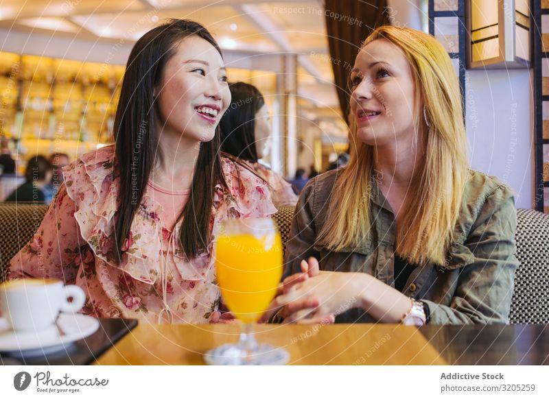 Multiethnische Freunde unterhalten sich im Café Freundschaft Sprechen Zusammensein Frau Jugendliche Person gemischter Abstammung Lächeln sitzen Tisch Lifestyle