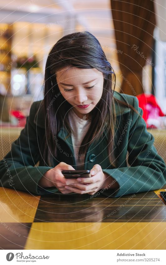 Asiatische Frau mit Smartphone im Café PDA benutzend sitzen Tisch asiatisch gemütlich Lifestyle Freizeit & Hobby urwüchsig ruhen Erholung Stil trendy elegant