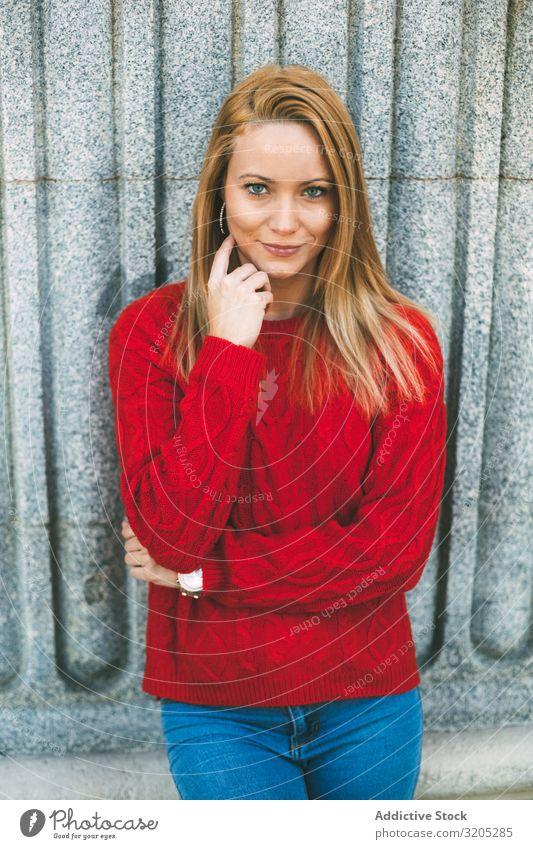 Stilvolle Frau, die in der Nähe einer Marmorwand steht Wand anlehnen Straße Großstadt Jugendliche Gebäude berührender Hals Pullover gestrickt trendy lässig
