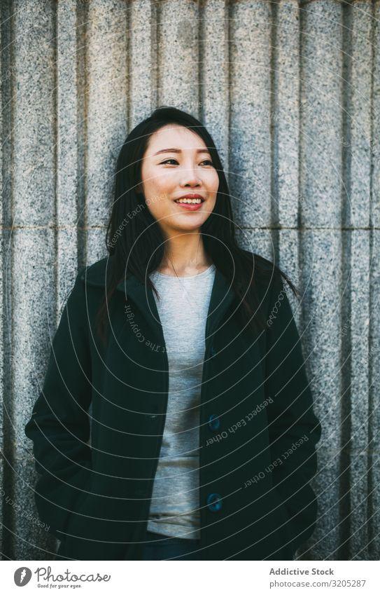Asiatische Frau an Marmorwand Wand anlehnen asiatisch Lächeln Jugendliche Straße Großstadt Gebäude elegant Mantel Stil trendy lässig urwüchsig Außenseite