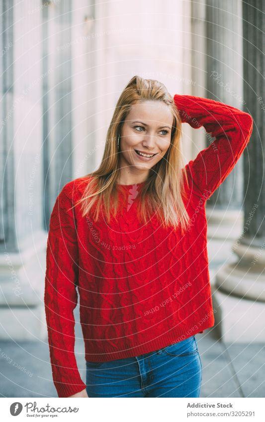Stilvolle Frau steht neben Marmorsäulen Porträt Glück Wegsehen Straße Großstadt Jugendliche Säule Gebäude Pullover gestrickt trendy lässig blond genießen