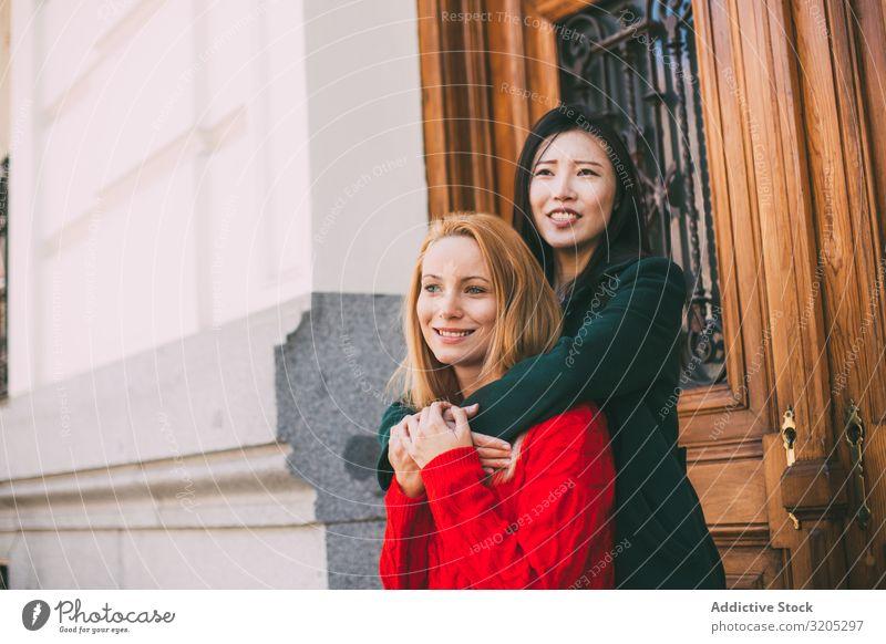 Fröhliche Freundinnen umarmen sich in der Nähe einer Ziertür Freundschaft Umarmen Lächeln Wegsehen Tür Straße Gebäude Großstadt Person gemischter Abstammung