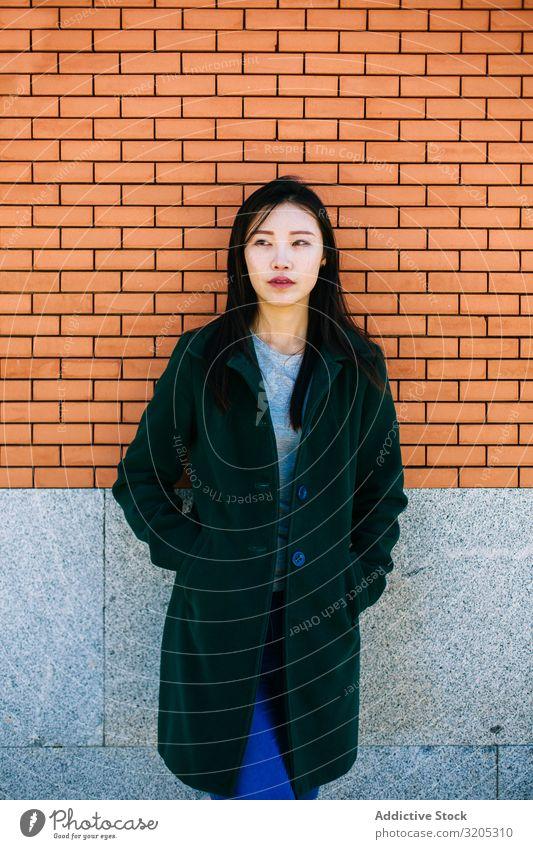 Nachdenkliche Asiatin, die an einer Ziegelmauer lehnt Frau Wand anlehnen besinnlich Wegsehen Straße Großstadt asiatisch urwüchsig Relief Oberfläche Lifestyle