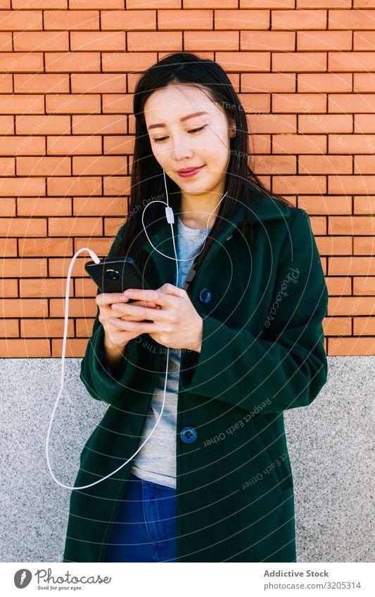 Asiatische Frau hört Musik in der Nähe einer Ziegelmauer hören PDA benutzend Wand anlehnen Backstein Straße Großstadt asiatisch urwüchsig Lifestyle