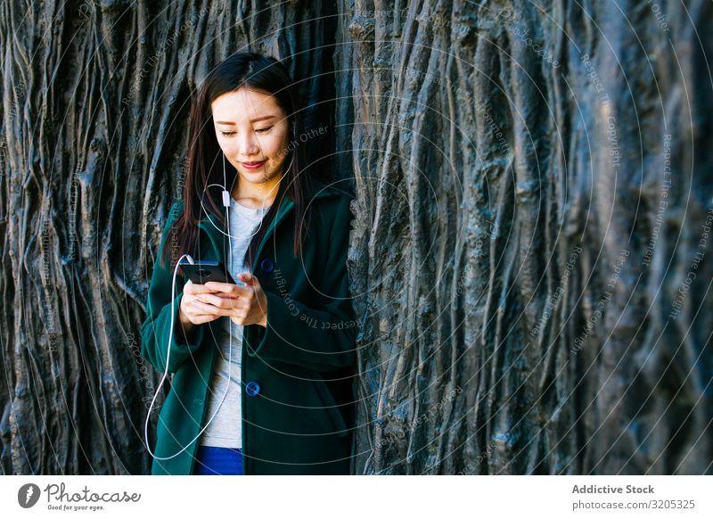 Asiatische Frau hört Musik in der Nähe einer rauen Wand hören PDA benutzend anlehnen Wurzel Baum Straße Großstadt asiatisch urwüchsig Relief Oberfläche
