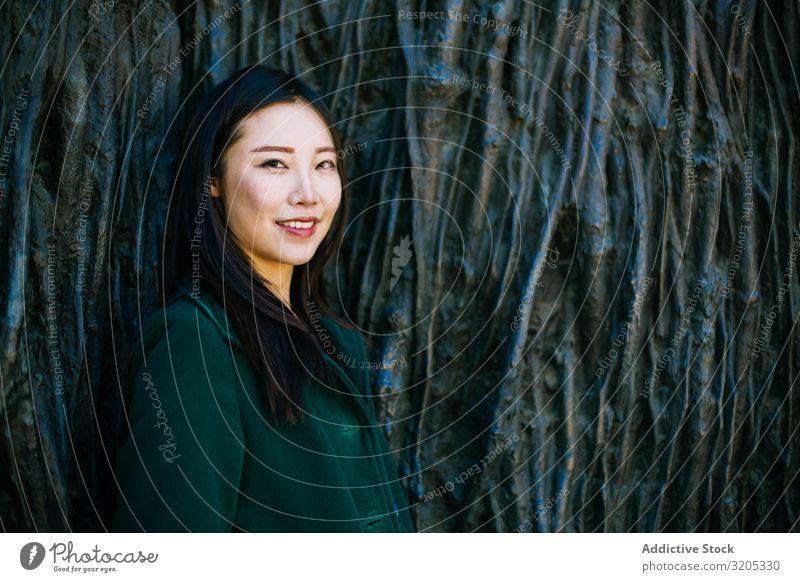 Fröhliche asiatische Frau lehnt an rauer Wand anlehnen Lächeln Wegsehen Wurzel Baum Straße Großstadt urwüchsig Relief Oberfläche Lifestyle Freizeit & Hobby